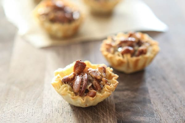 pecan bites with bites in background on parchment paper