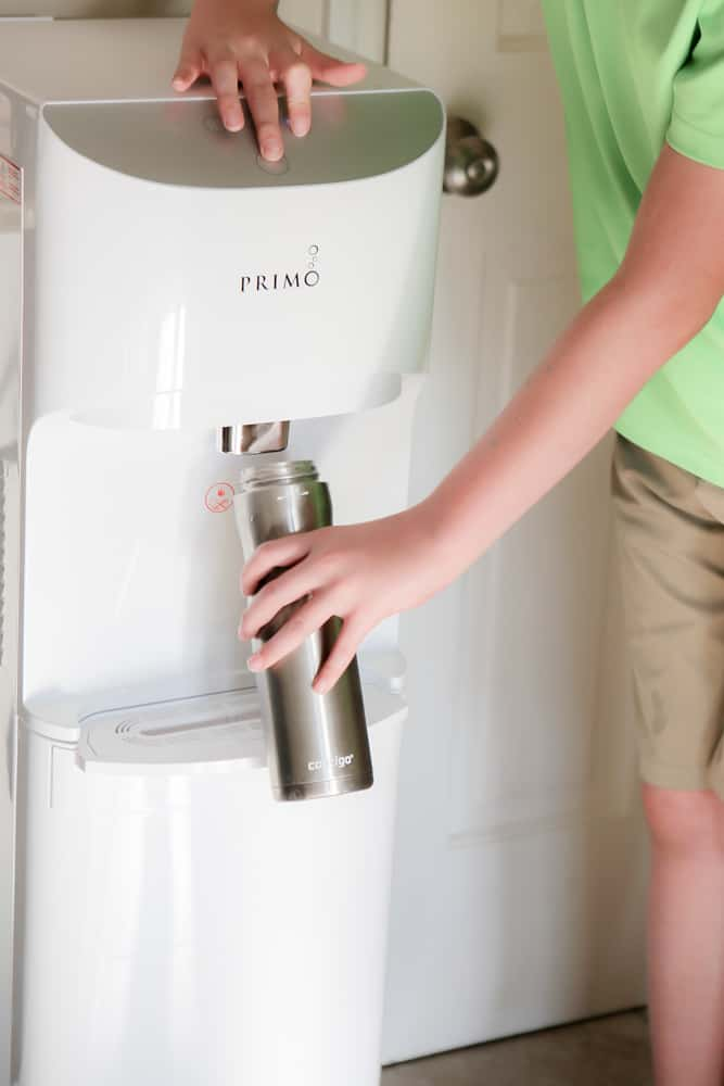 boy getting water from primo dispenser
