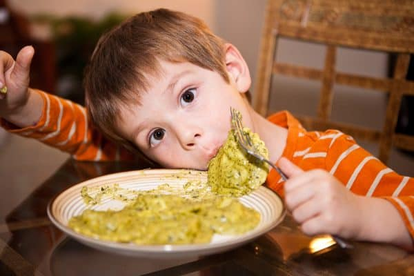 child eating pesto pasta