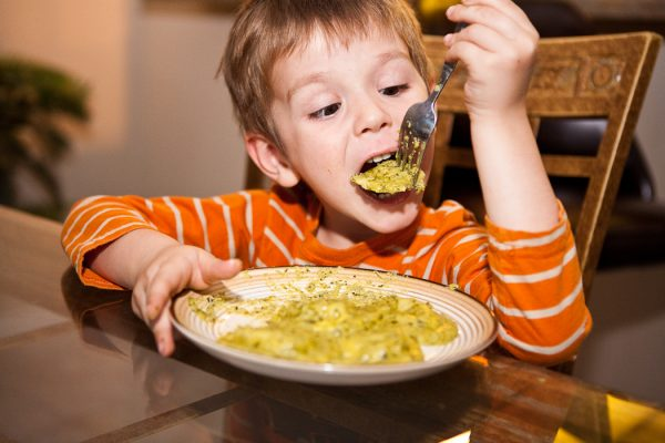 child eating ravioli