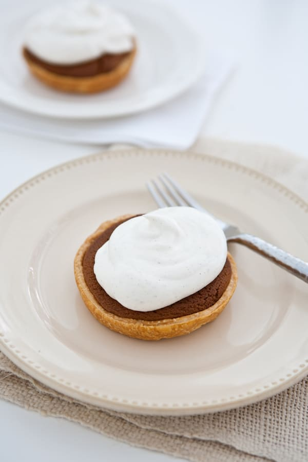 Mini Gingerbread Cookie Pies with Spiced Cream close up beige plate