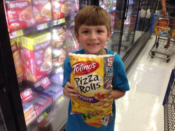child holding totinos pizza rolls