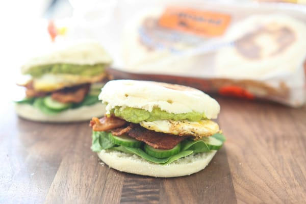 closed bacon avocado egg sandwich on cutting board