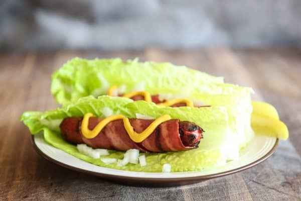 bacon wrapped hot dogs in lettuce bun on white plate