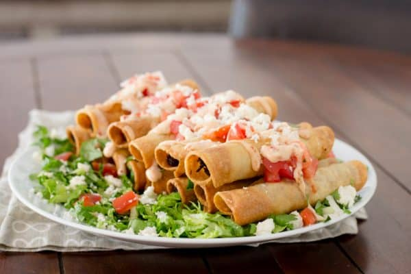 taquitos on white plate on brown table