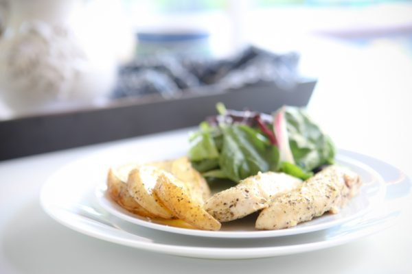 Roasted Lemon Garlic Herb Chicken Breasts with Roasted Potatoes and salad on white plate