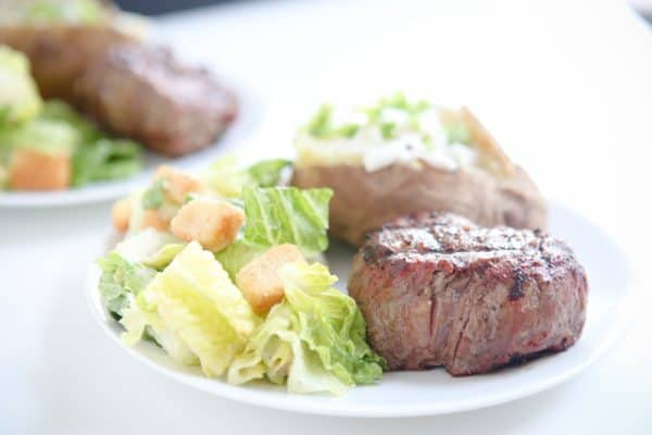 steak, caesar salad, and potato on white plate