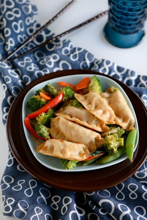 potstickers on blue and brown plates with chopsticks