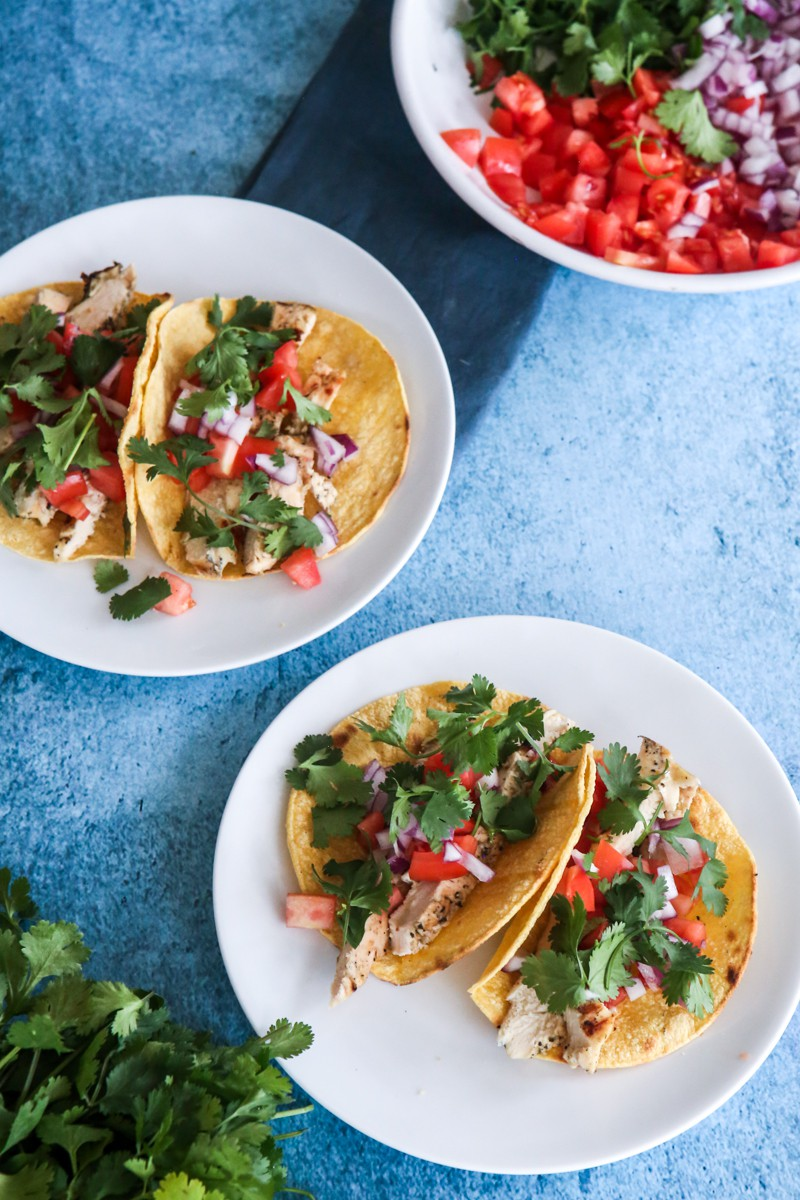 tacos with vegetables overhead view blue background