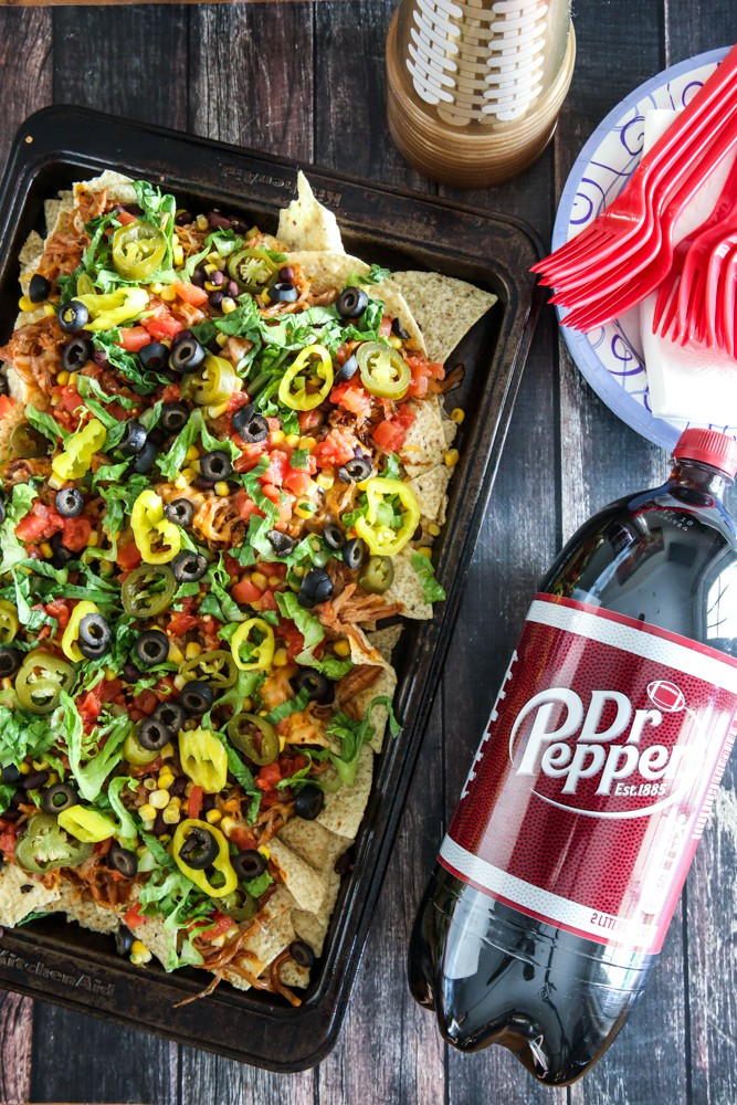 puled pork nachos in black pan with dr. pepper brown background