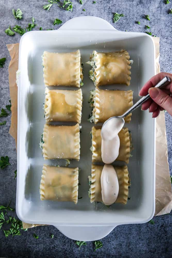 lasagna roll ups with sauce being spread