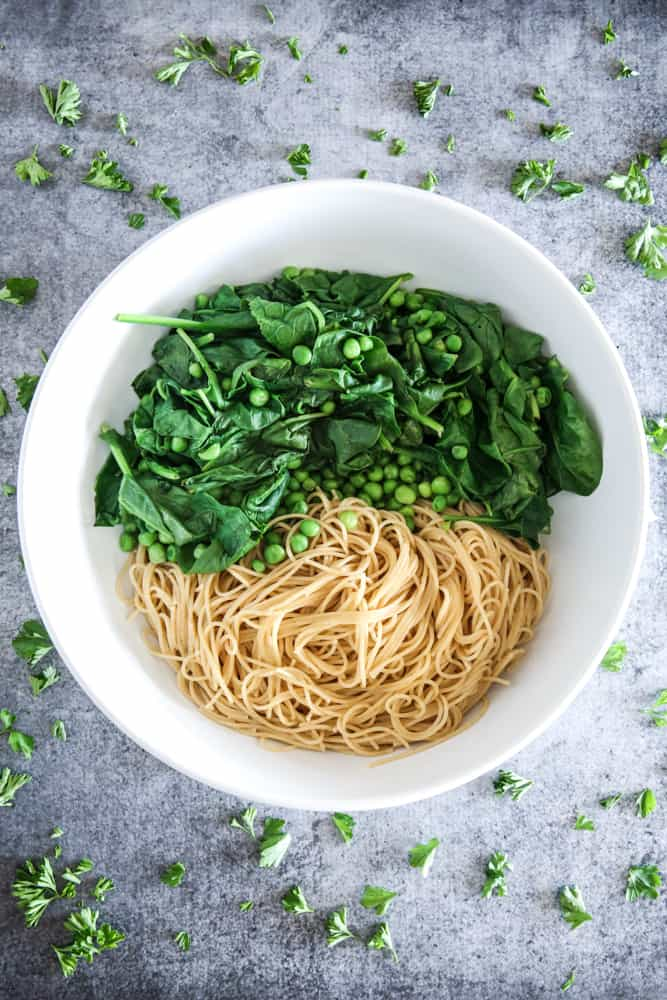 spaghetti spinach and peas in white bowl