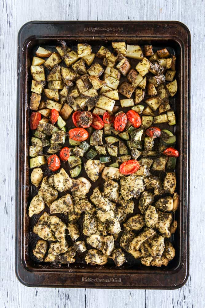 baked pesto chicken and potatoes grey background