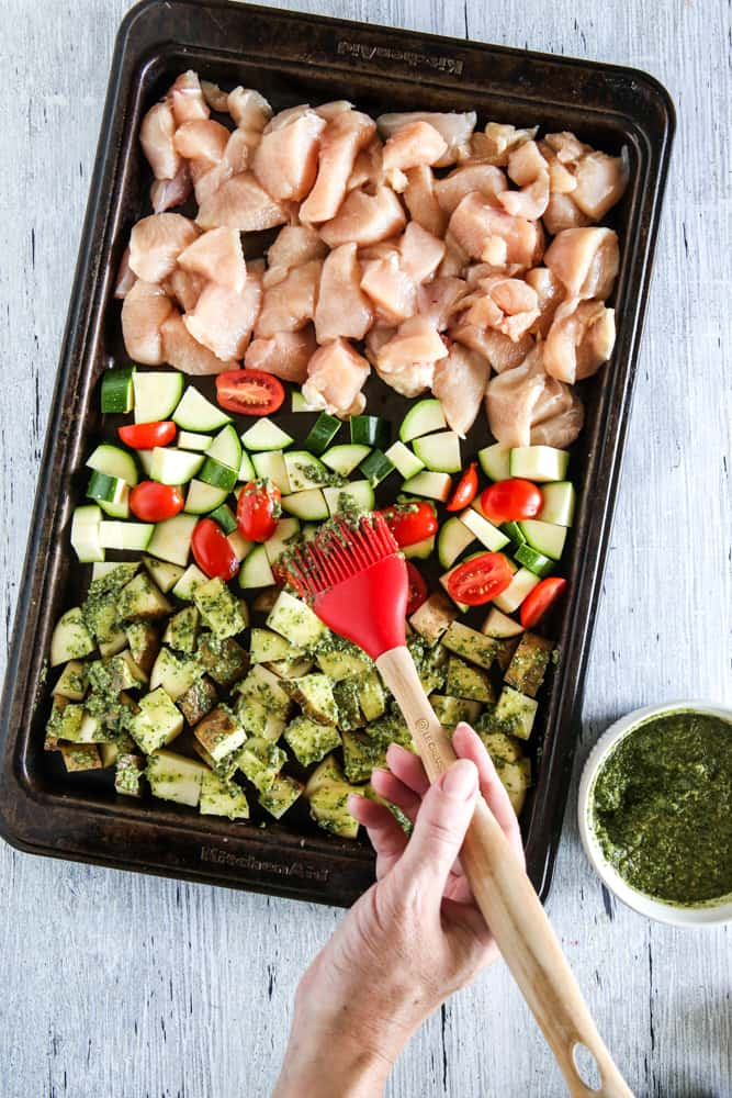 chicken and vegetables being brushed with pesto