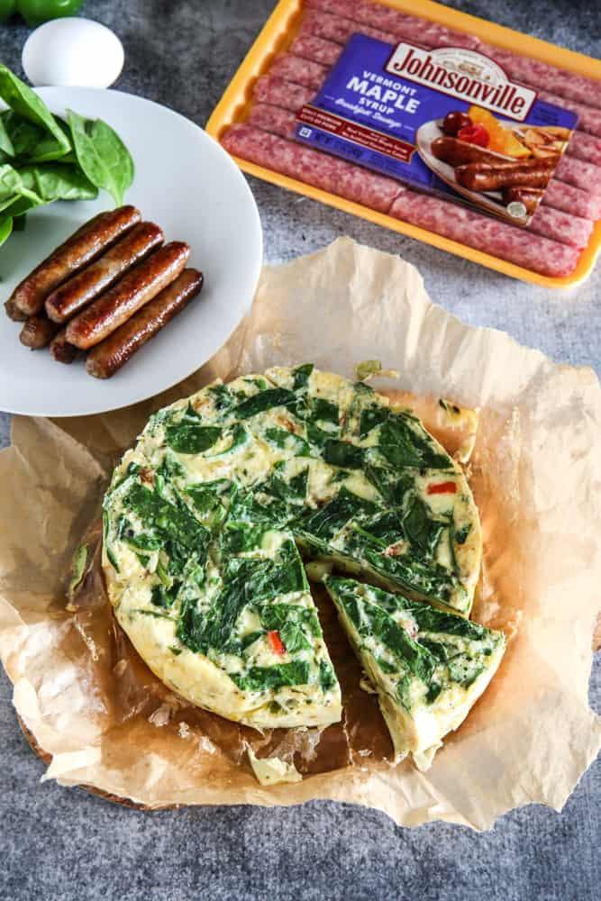 tortilla española with plate of spinach and sausages