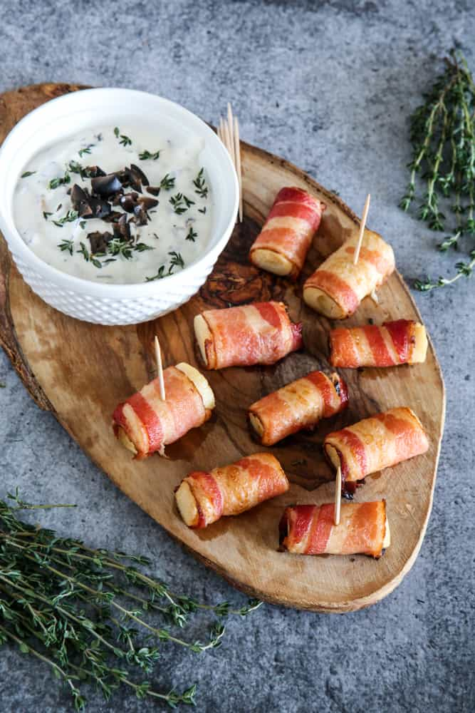 bacon wrapped hearts of palm and dip on cutting board