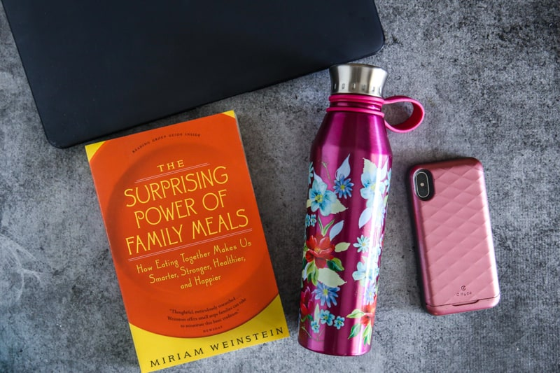 water bottle, phone, laptop, and The Surprising Power of Family Meals book