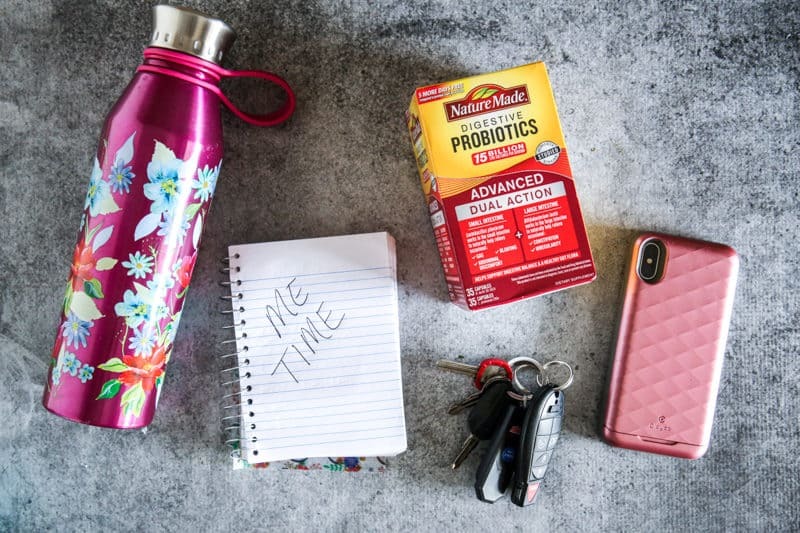water bottle, notebook, car keys, probiotics, and phone overhead view