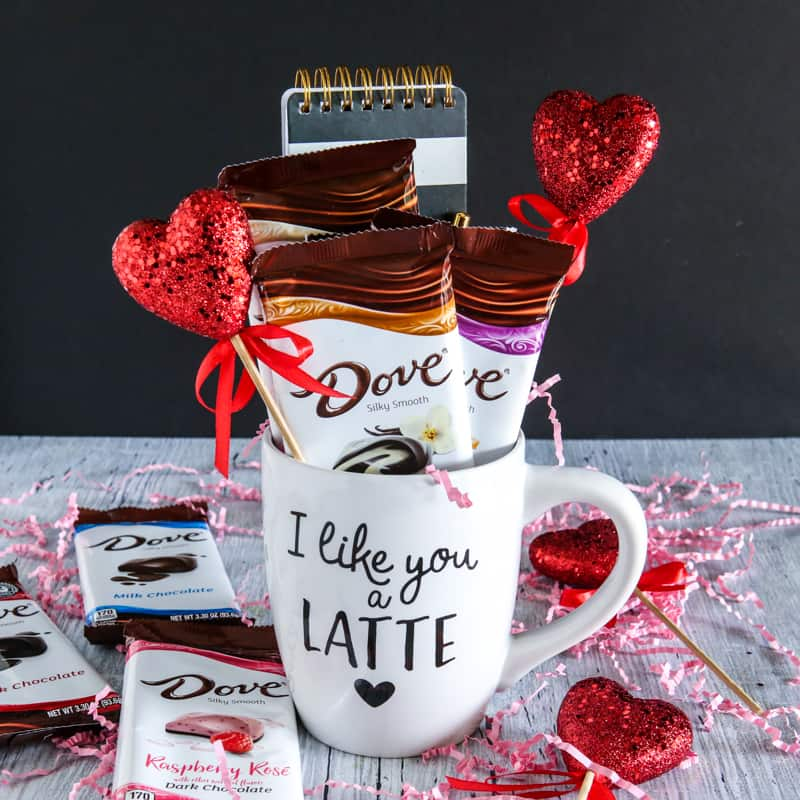 dove chocolate bars in coffee mug with notepad, pink confetti, and heart toothpicks. grey background