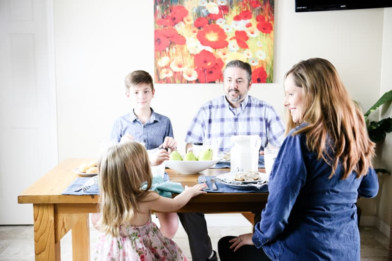 family sitting at breakfast table with pears beige wall