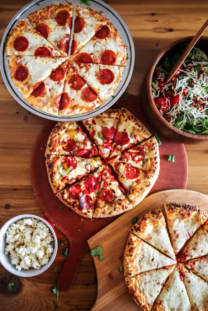 pizzas on platters with salad in brown bowl and popcorn in red and white bowl overhead view brown background