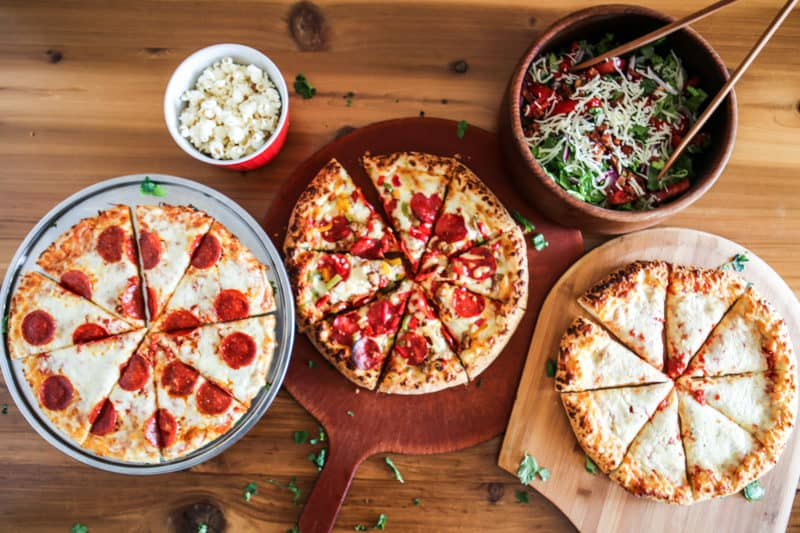 three sliced pizzas with popcorn and salad overhead view