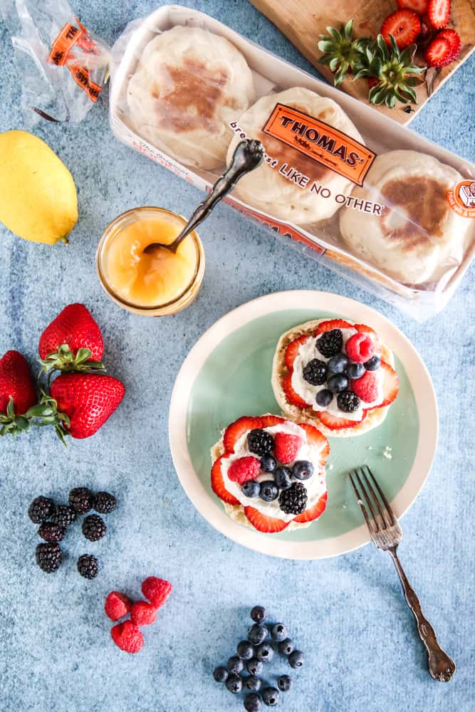 two english muffins with lemon curd and strawberries light blue background