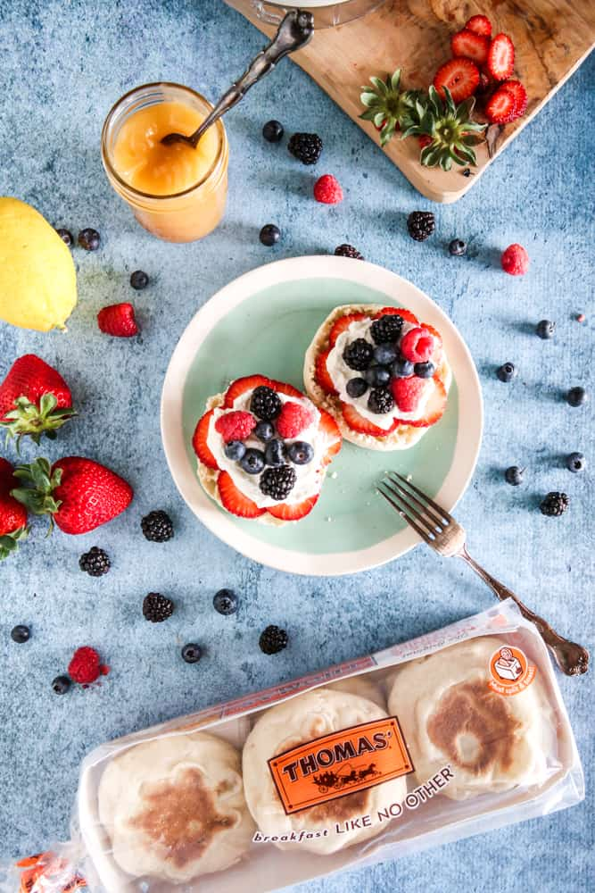 plate of english muffins on light blue background and fork with assorted berries