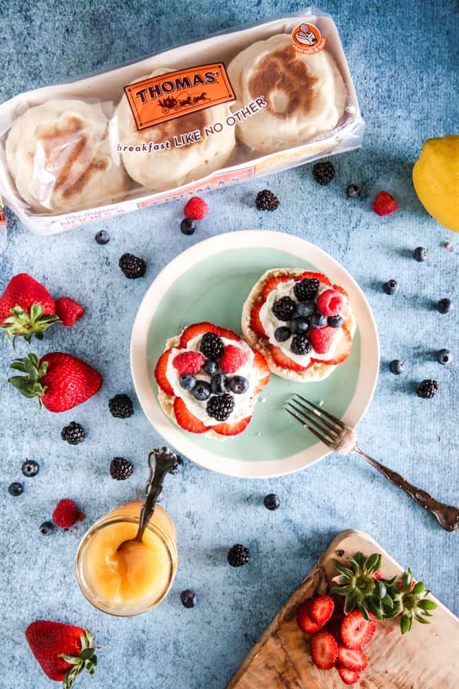package of thomas english muffins with english muffins and strawberries on light blue plate with fork and lemon curd light blue background