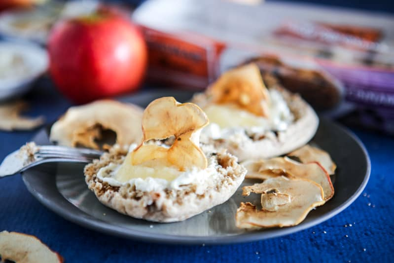 focused on two english muffins with apple sauce, cream cheese and apple slices