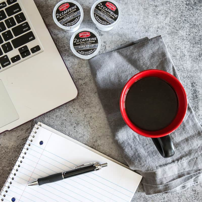 cup of extra caffeine coffee with notepad and laptop