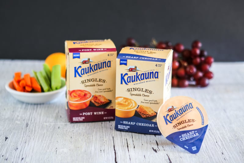 boxes of kaukauna cheese singles with fruits in back white background