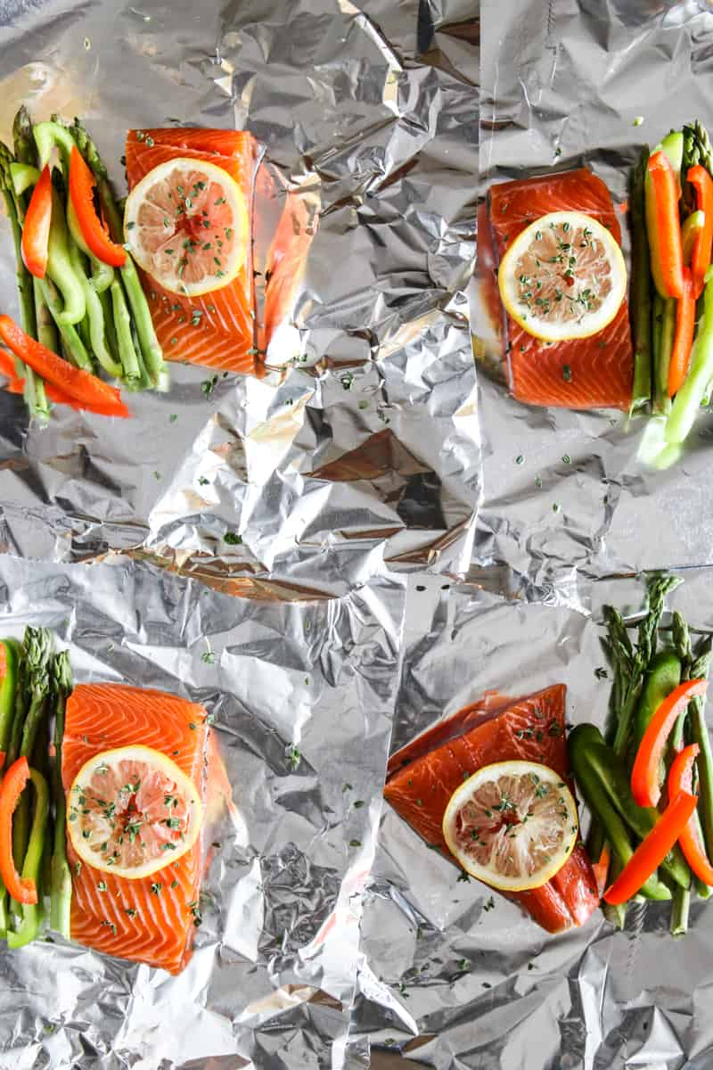 four cuts of raw salmon with lemons on top