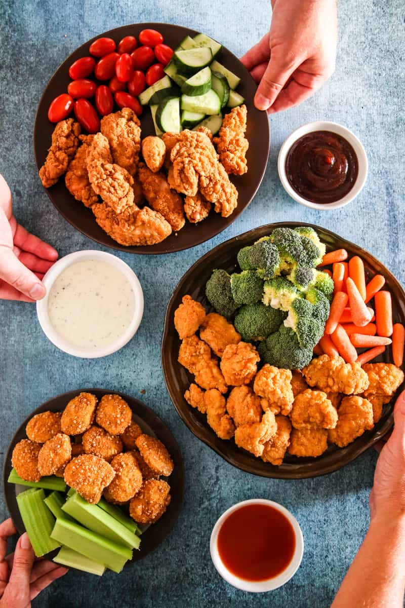 three plates of tyson chicken and vegetables with dip