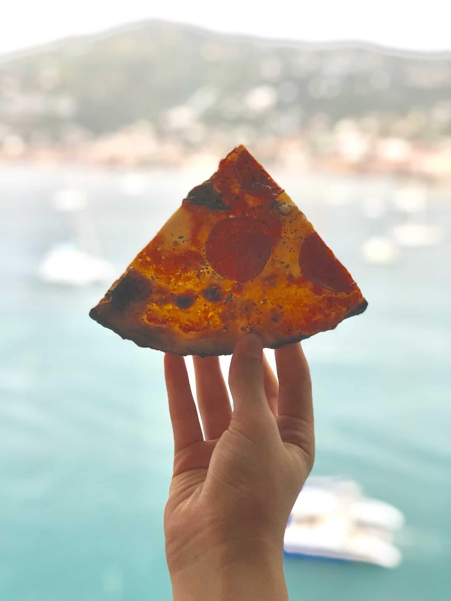 pizza being held against ocean