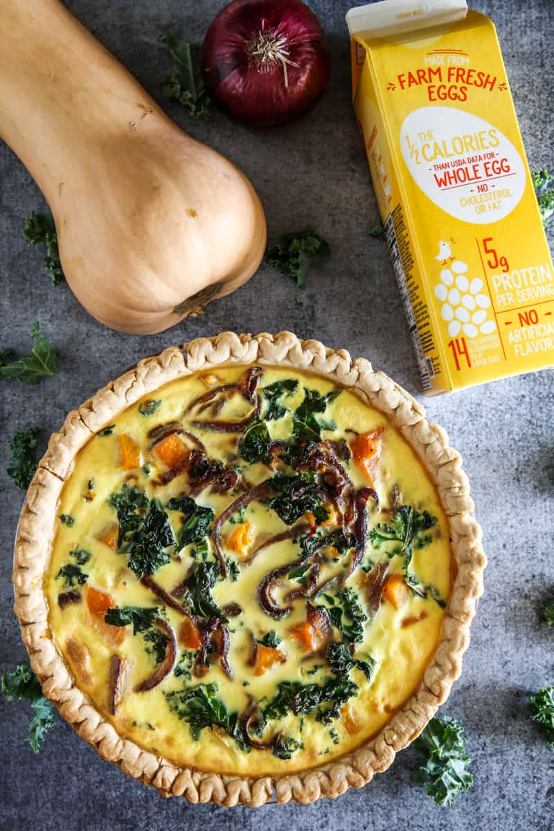 birds eye view of butternut squash quiche and carton off egg beaters on grey background
