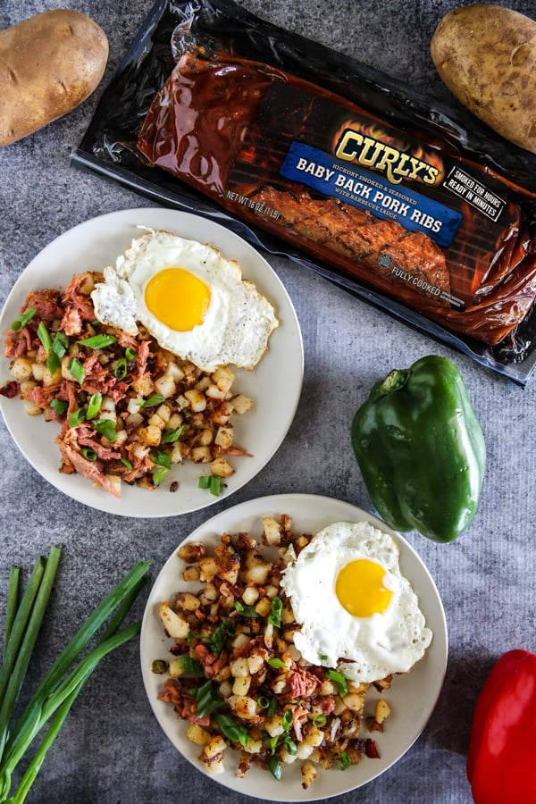 bbq rib hash with eggs on grey background with vegetables