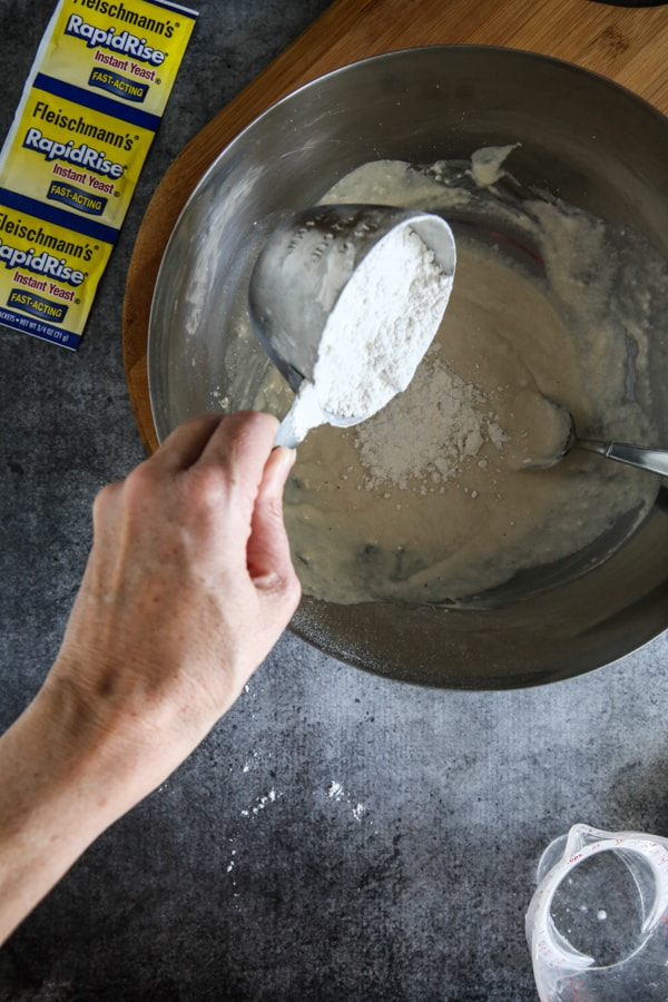 adding more flour to yeast dough in bowl